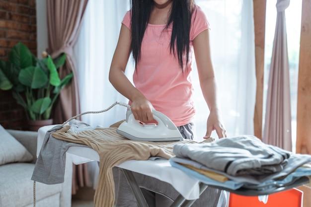 집에서 방에있는 다리미판에 옷을 다림질하는 십 대 소녀