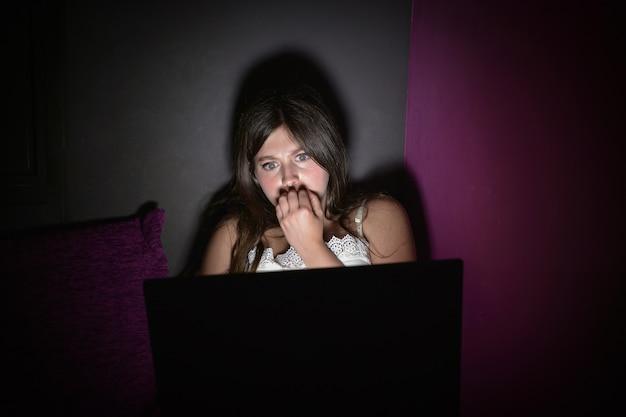 Teenage girl is afraid to watch a horror movie