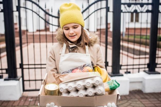 10 대 소녀가 코로나 바이러스가 유행하는 동안 노인에게 식료품을 배달하고 있습니다.