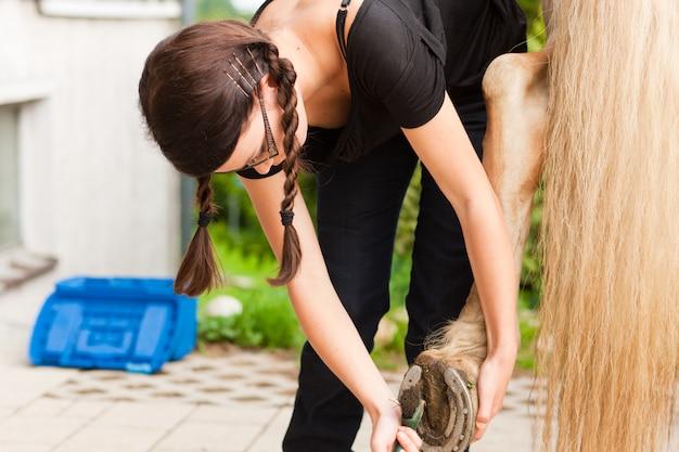 Teenage girl is grooming her horse outdoors
