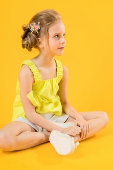 A teenage girl is sitting on yellow background.