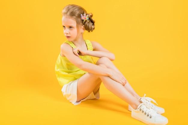 A teenage girl is sitting on yellow tshirt.