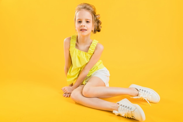 A teenage girl is sitting on yellow .