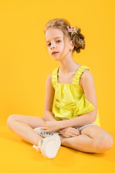 A teenage girl is sitting on a yellow  .