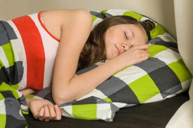Teenage girl is sleeping at home in bed