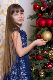 A teenage girl is standing near a festive christmas tree. new year christmas