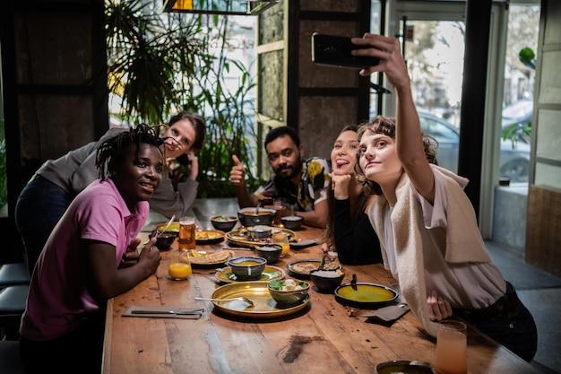 Девочка-подросток делает селфи со своими друзьями, используя камеру своего смартфона
