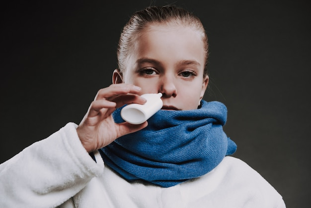 Teenage girl in knit scarf drips drops in nose.