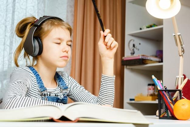 십대 소녀 음악 듣기 및 학교 숙제, 학습 및 공부 개념