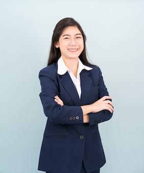 10代の少女の長い髪は、青い背景にスーツと白いシャツを着て腕を組んで立っています