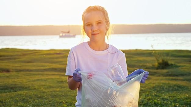 川岸に集められたゴミの袋を持ってカメラを見ている10代の少女。