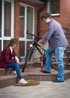 壊れた自転車を修理する父を探している10代の少女