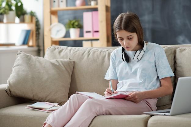 家庭環境でラップトップの前にソファで家の割り当てを準備しながらコピーブックにメモをとる10代の少女