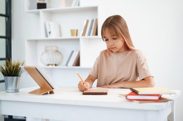 집에 있는 테이블에서 숙제를 하는 메모장에 메모를 하는 10대 소녀
