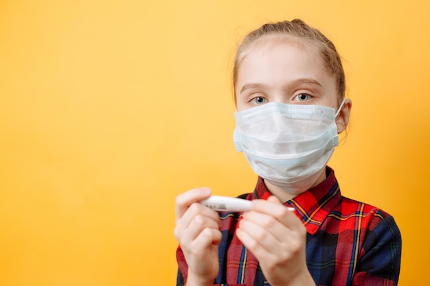 A teenage girl in a medical mask holding a medical thermometer