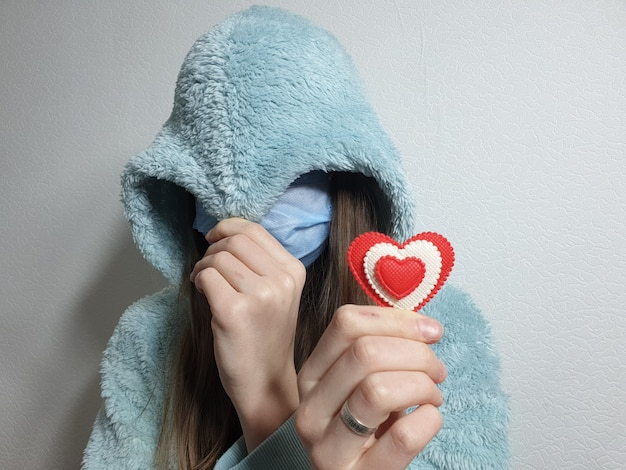 Teenage girl in a medical mask holds a red heart in her hand, valentine's day in quarantine