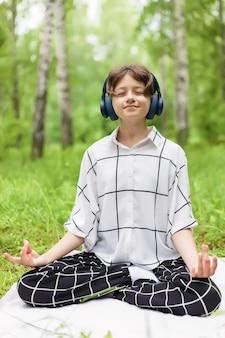 10代の少女は、夏の間、屋外でヘッドフォンで音楽を聴いて蓮華座で瞑想します