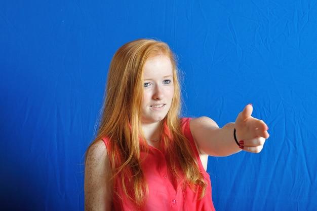銃を持っているジェスチャーを模倣する10代の少女