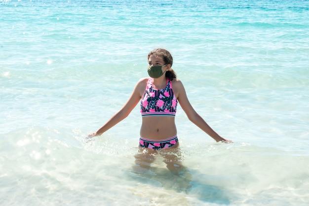 コロナウイルス病を防ぐために防護マスクを着てビーチで10代の少女