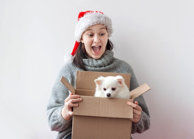 A teenage girl opens a cardboard box and there's a little pomeranian dog.
