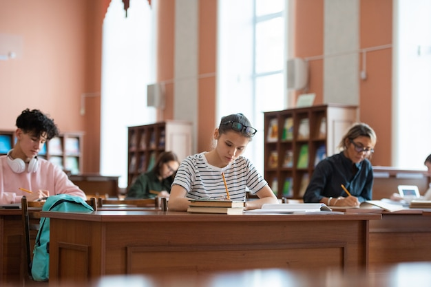 Teenage girl and other college learners sitting by desks in library and making notes in copybooks while preparing for seminar