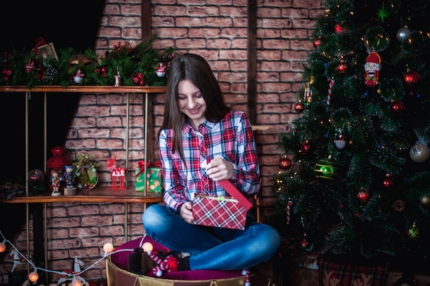 Teenage girl in a plaid shirt opens box christmas gift
