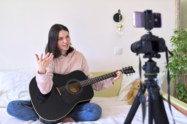 Teenage girl playing an acoustic guitar, talking with followers, recording video for channel, blog. hobbies for girls, music, art, education, online communication with children and adolescents