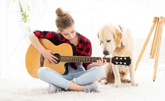 自宅でかわいい犬と一緒にギターを弾く 10 代の少女