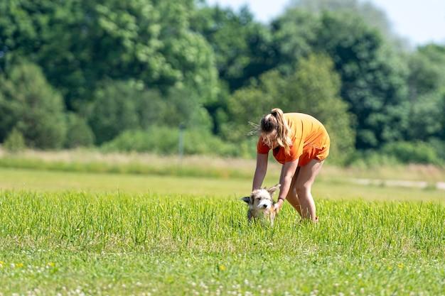Девочка-подросток играет на лужайке со щенком смешанной породы в солнечный летний день