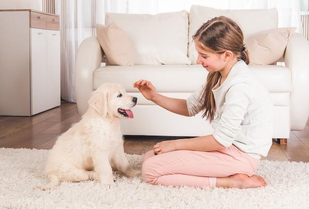 家でかわいい子犬と遊ぶ10代の少女