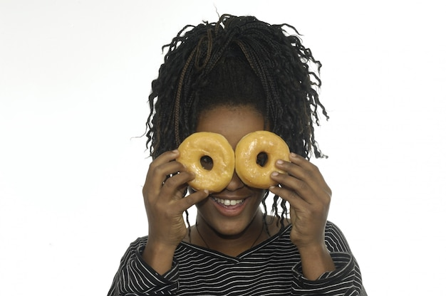 Teenage girl playing with donuts