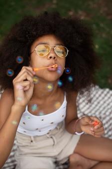 シャボン玉で遊ぶ10代の少女
