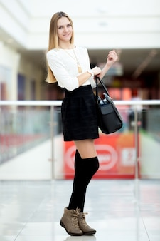 Teenage girl posing in fashionable outfit in shopping mall