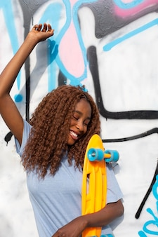 Teenage girl posing at park with skateboard