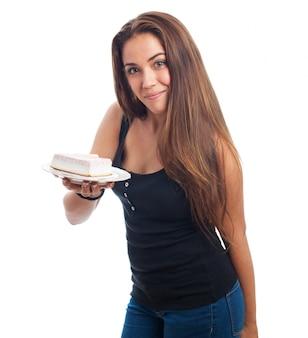 プレート上のデザートでポーズ十代の少女。