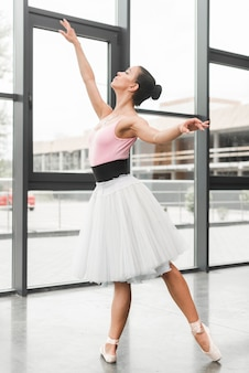 Teenage girl practicing ballet dance near glass wall