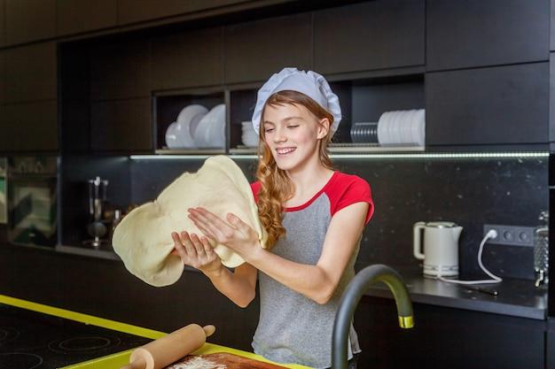Teenage girl preparing dough, bake homemade holiday apple pie in kitchen