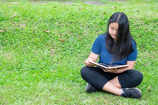 夏の公園で本を読んでいる十代の少女。
