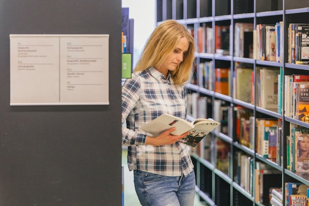Teenage girl reading book at shelf