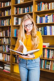 Teenage girl reading book standing at shelves