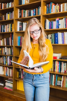 Teenage girl reading book standing at shelves