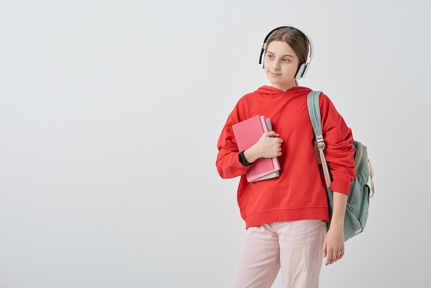 Teenage girl in red hoodie and white jeans holding books by chest and listening to her favorite music in headphones in isolation