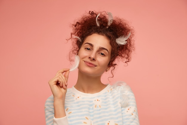 10代の少女、巻き毛の赤毛の女性。うさぎのストライプのセーターを着て、頬を羽で触る。パステルピンクの壁の上の孤立したクローズアップ