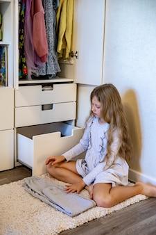 10代の少女が服を丸めて食器棚にアパレルを置くマリーコンドス法を使用