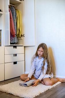 10대 소녀가 옷을 말아서 찬장에 의복을 넣는 마리 콘도스 방법을 사용합니다.