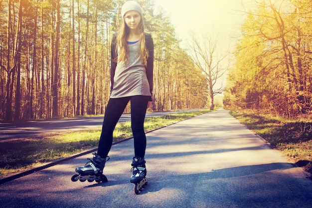 Teenage girl on roller skates at summer.