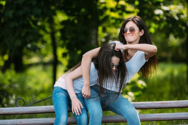 Teenage girl rubbing sisters head outside