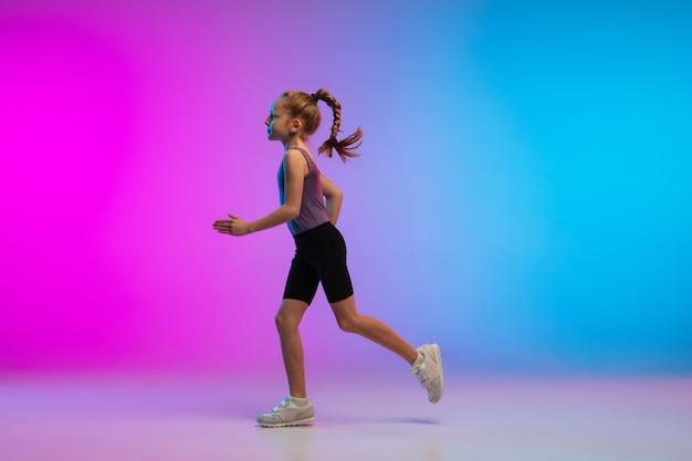動いているグラデーションピンクブルーのネオンスタジオの背景に対してジョギングしている10代の少女