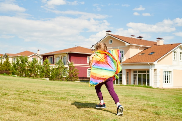 Teenage girl running with colorful kite