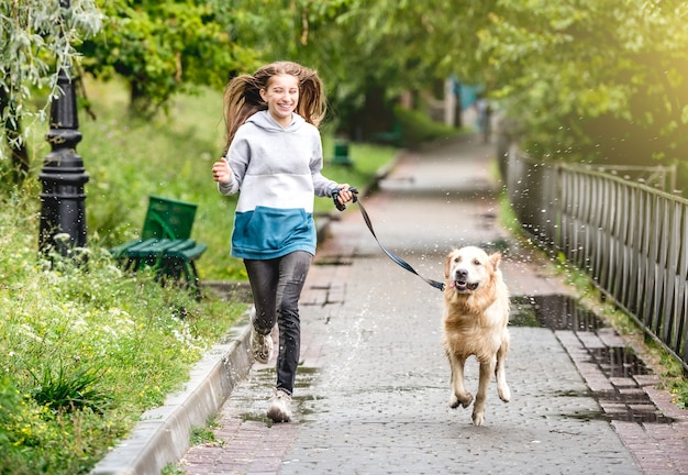 Teenage girl running with golden retriever dog in park after rain